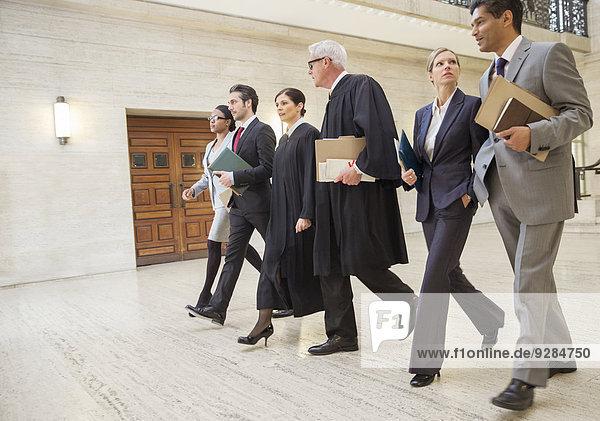 Richter und Anwälte gehen gemeinsam durchs Gerichtsgebäude.