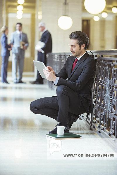 Rechtsanwalt bei der Arbeit am digitalen Tablett im Gerichtsgebäude