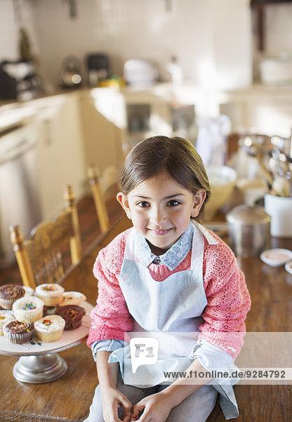 Junges Mädchen auf Küchentisch bei Muffins sitzend