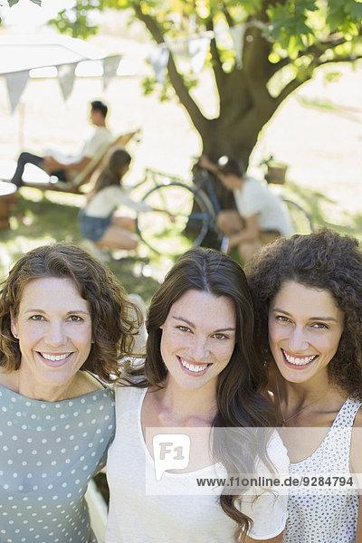 Drei Frauen  die sich im Freien umarmen.