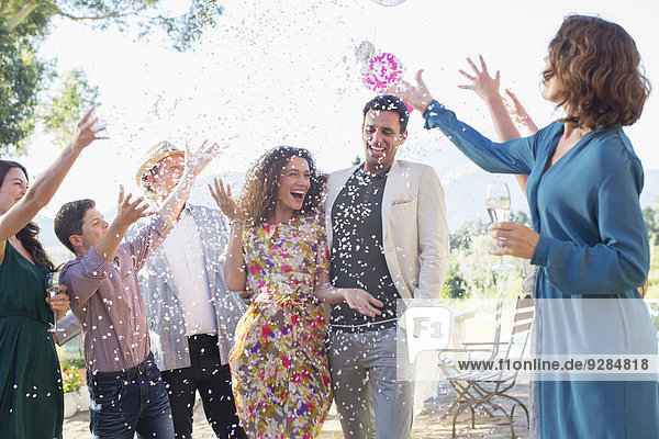 Familie wirft Konfetti auf frisch verheiratetes Paar