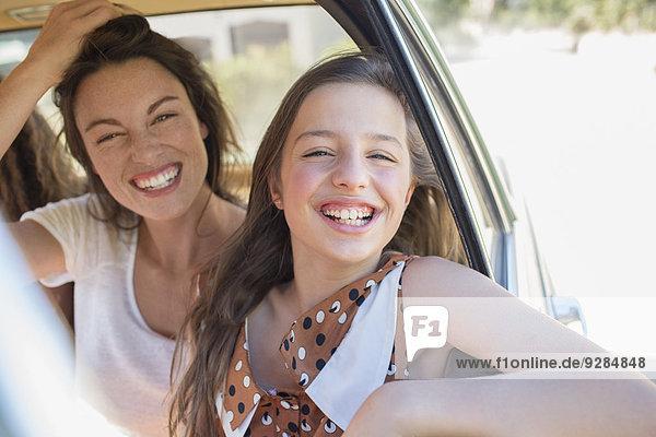 Schwestern lachen auf dem Rücksitz des Autos