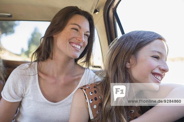 Schwestern  die zusammen auf dem Rücksitz sitzen.