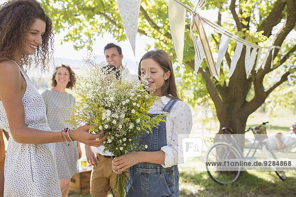 Frau bewundert Blumen  die von einem jungen Mädchen gehalten werden