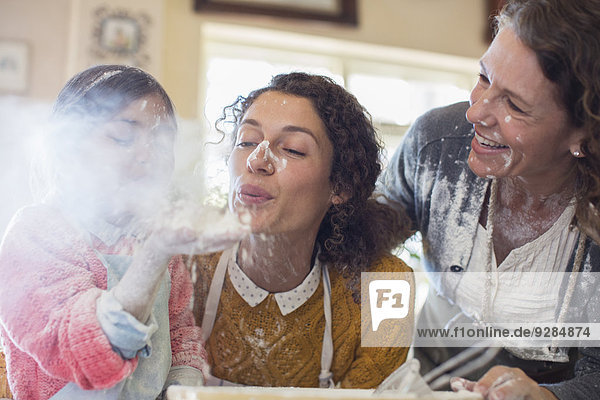 Drei Generationen von Frauen spielen mit Mehl