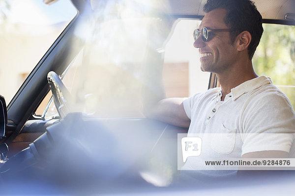 Mann fährt Auto an einem sonnigen Tag