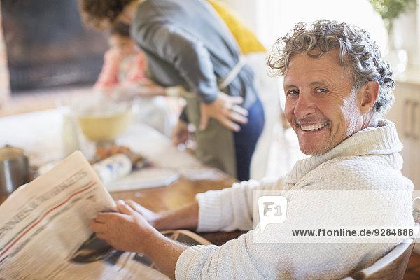 Älterer Mann liest Zeitung in der Küche