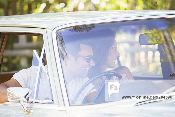 Paar genießt Autofahrt an einem sonnigen Tag