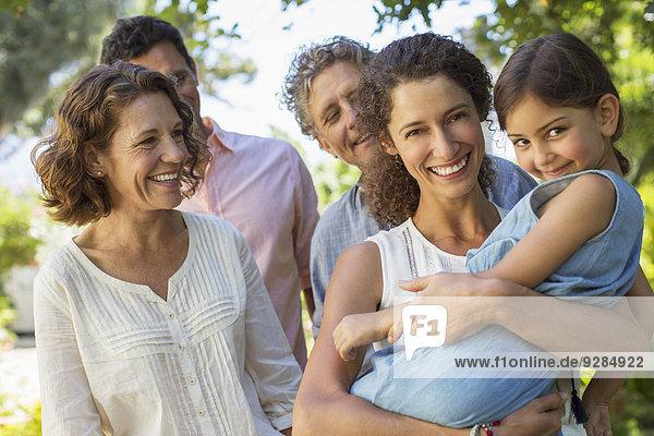 Mutter mit Tochter in den Armen mit Familie im Freien