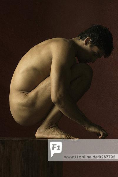 Nackter Mann kauernd mit Kinn auf Knien  Seitenansicht Nackter Mann kauernd mit Kinn auf Knien, Seitenansicht