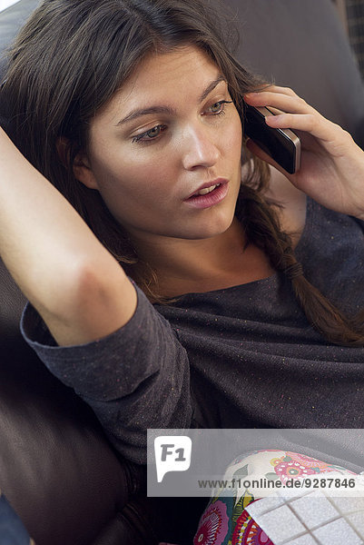 Woman reclining on sofa talking on cell phone