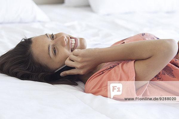 Frau auf dem Bett liegend  mit dem Handy chattend