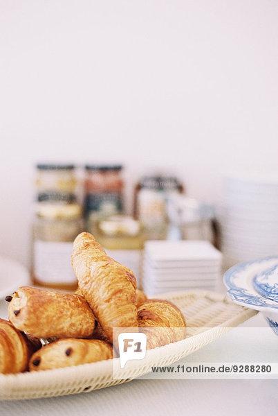 Ein Tisch mit einer Schüssel Croissants und Pains au chocolat. Ein Tisch mit einer Schüssel Croissants und Pains au chocolat.