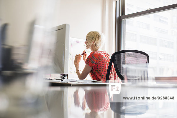 Büroalltag. Eine junge Frau arbeitet an einem Büroschreibtisch.