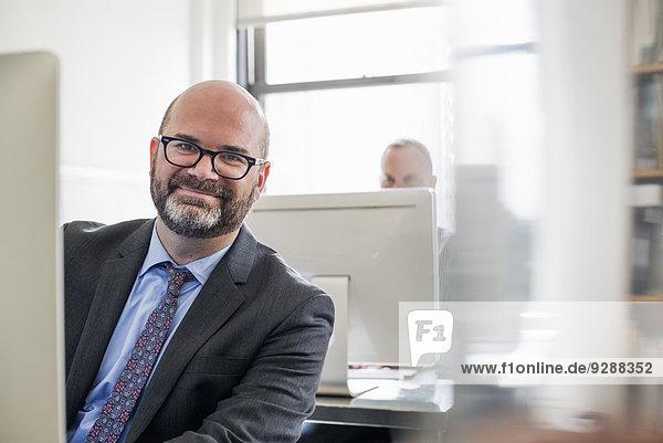 Büroalltag. Ein Mann in Anzug und Krawatte sitzt an seinem Schreibtisch und sieht sich am Computer um.