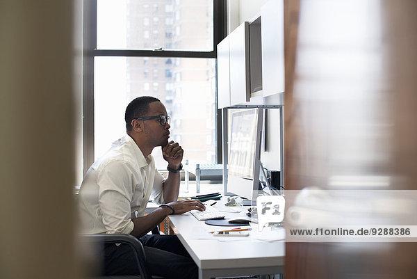 Ein Mann  der in einem Büro arbeitet und an einem Schreibtisch sitzt. Er schaut auf einen Computerbildschirm.