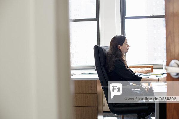 Eine Frau  die in einem Büro arbeitet und an einem Schreibtisch sitzt.