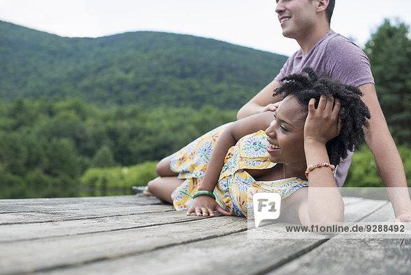 Ein Paar entspannt sich auf einem Steg mit Blick auf einen Bergsee.