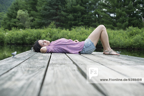 Eine Frau  die im Sommer auf dem Steg an einem See liegt