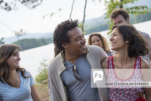 Eine Gruppe von Menschen  die einen gemütlichen Spaziergang an einem See genießen.