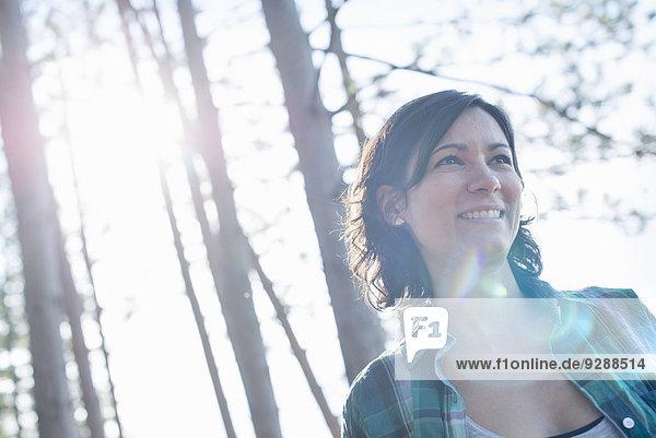 Eine Frau geht im Sommer durch den Wald.