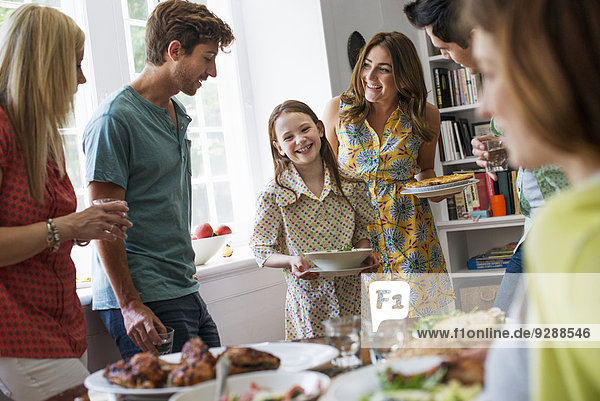 Ein Familientreffen zum Essen. Erwachsene und Kinder an einem Tisch.