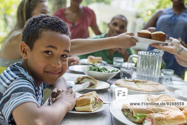 Ein Familientreffen  Männer  Frauen und Kinder um einen Tisch in einem Garten im Sommer. Im Vordergrund ein lächelnder Junge.