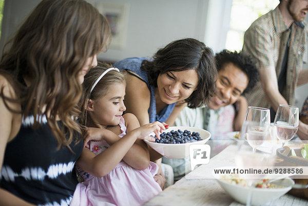 Ein Familientreffen zum Essen. Erwachsene und Kinder an einem Tisch. Ein Familientreffen zum Essen. Erwachsene und Kinder an einem Tisch.