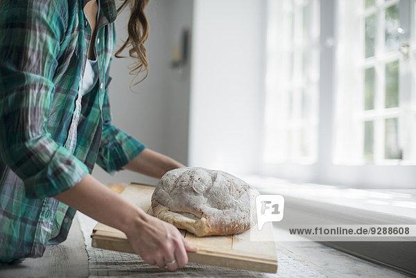 Ein Familientreffen. Eine Frau trägt einen frisch gebackenen Laib Brot. Ein Familientreffen. Eine Frau trägt einen frisch gebackenen Laib Brot.