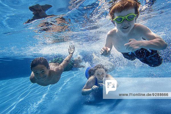 Three children swimming underwater  smiling at the camera.