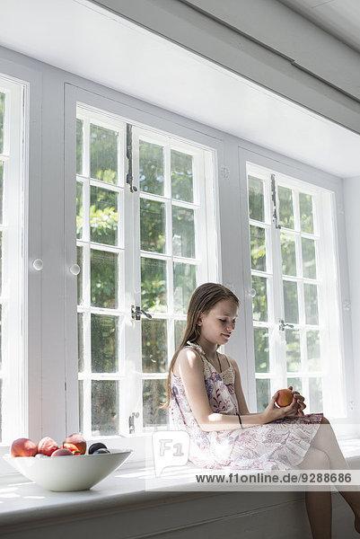 Mädchen am Fenster sitzend.