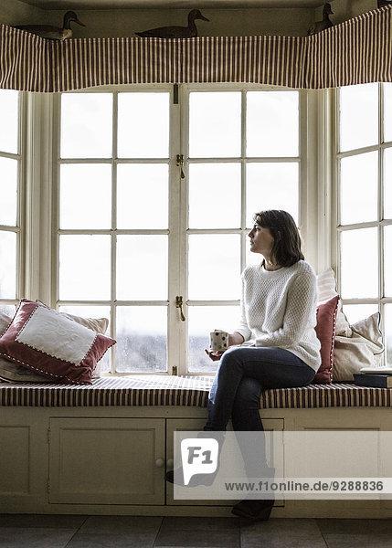 Eine junge Frau sitzt an einem Fensterplatz  mit einer Tasse Tee.