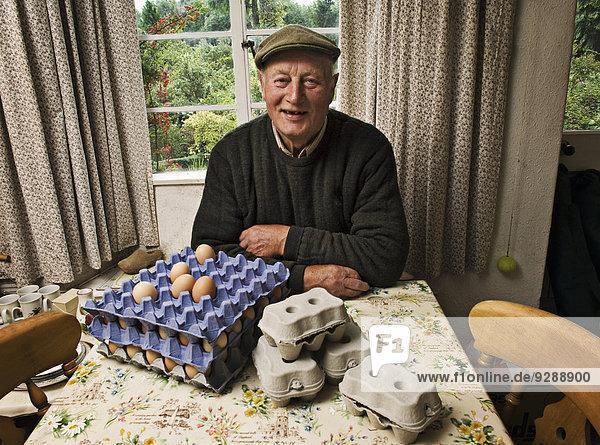 Ein Bauer  der an einem Tisch in einem Bauernhaus mit Tabletts mit frischen Eiern sitzt.