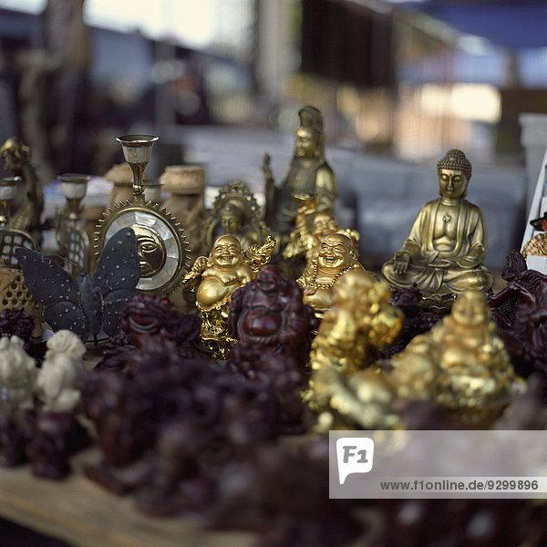 Eine Sammlung verschiedener Buddha-Statuen zum Verkauf auf einem Flohmarkt