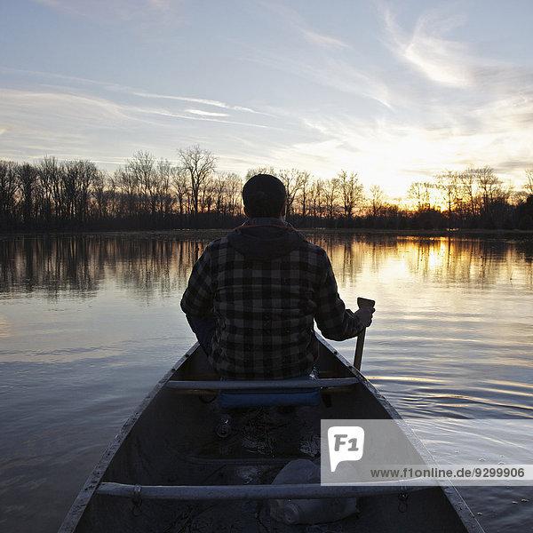 Ein Mann im Kanu auf einem See bei Sonnenuntergang  Rückansicht