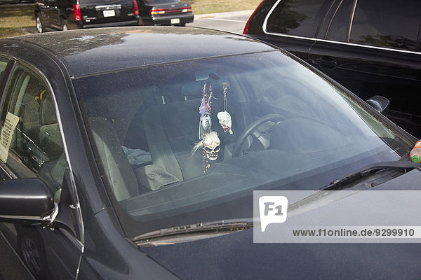 Ein Schädel und verschiedene andere Verzierungen  die am Rückspiegel eines Autos hängen.
