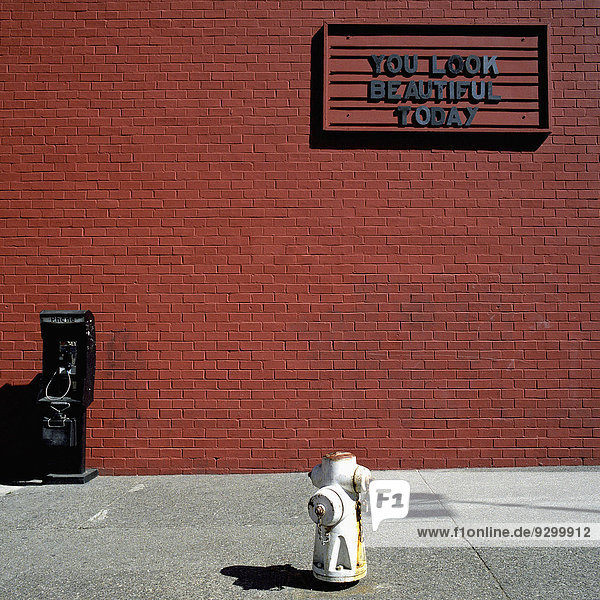 Ein Schild mit der Aufschrift You Look Beautiful Today auf einer roten Ziegelwand.