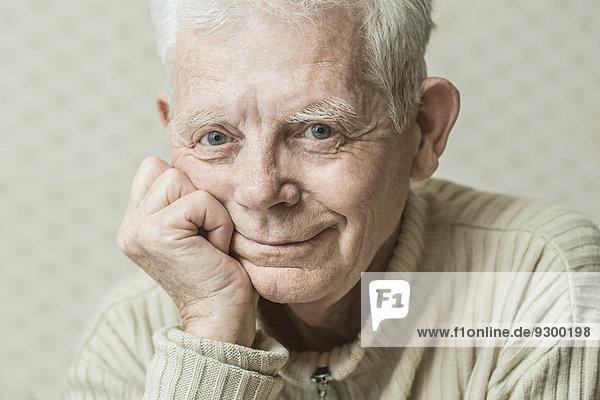 Nahaufnahme eines lächelnden älteren Mannes mit Hand am Kinn