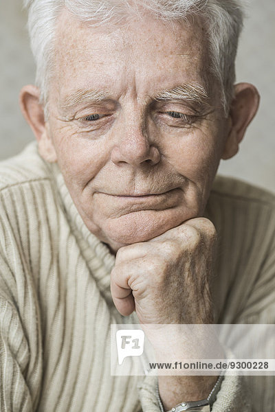 Close-up of thoughtful senior man with hand on chin