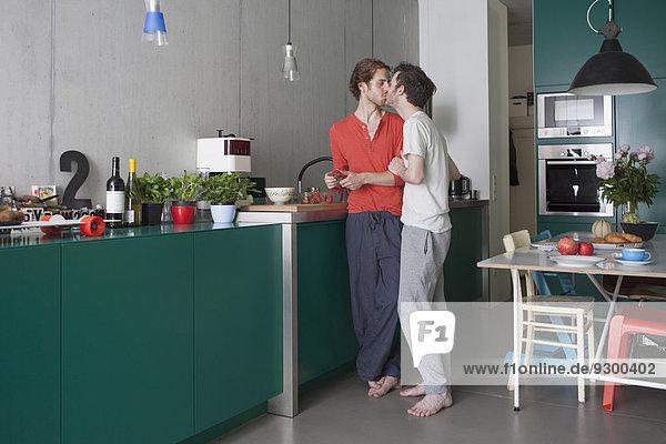 Volle Länge des romantischen schwulen Paares  das sich in der Küche küsst.