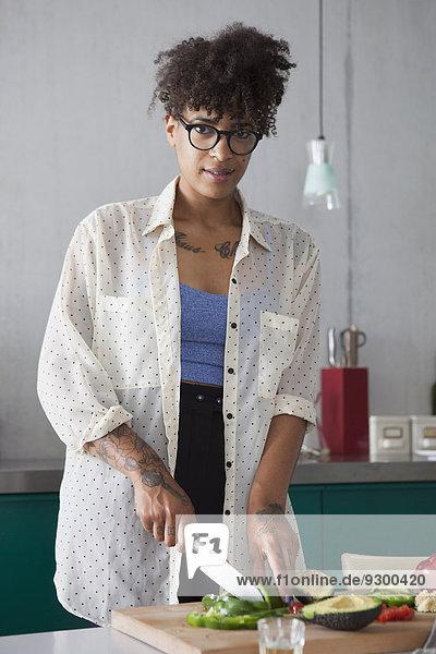Porträt einer jungen Frau  die in der Küche Gemüse schneidet.
