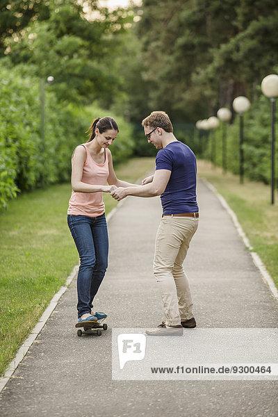 Mann assistierende Frau beim Skateboarden auf dem Fußweg