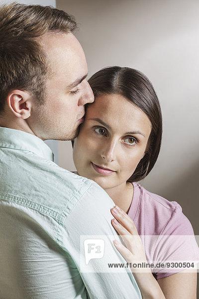 Rückansicht des Mannes  der die Frau zu Hause küsst.