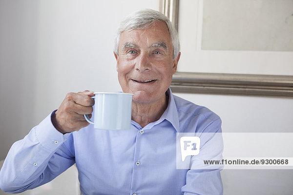 Porträt eines glücklichen älteren Mannes mit Kaffeetasse zu Hause