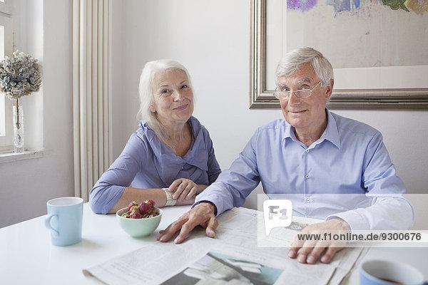 Porträt eines glücklichen älteren Paares mit Zeitung am Tisch