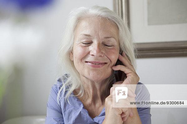 Entzückende Seniorin  die zu Hause ans Handy geht