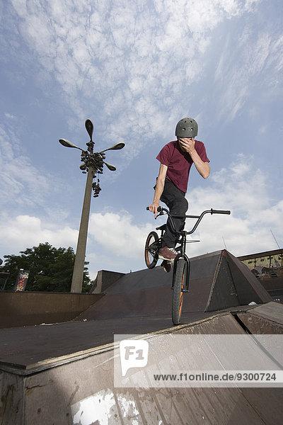 Ein junger Mann  der auf einem BMX-Bike auf einer Rampe balanciert.