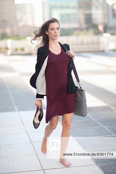 Junge Geschäftsfrau geht barfuß und trägt High Heels