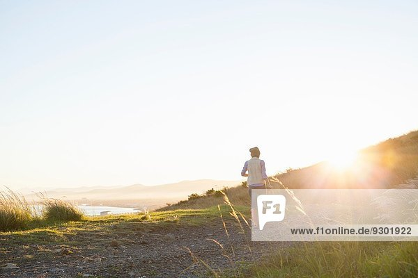Young woman walking on hill at sunset