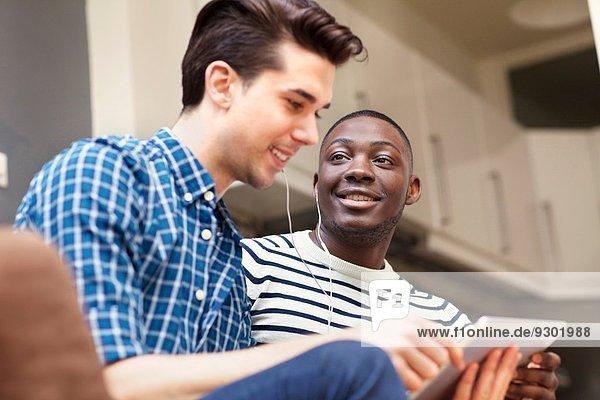 Zwei junge Männer hören Musik auf digitalem Tablett auf dem Sofa im Wohnzimmer.